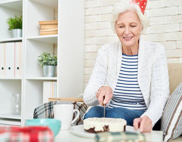 Seniorin bei Kaffee und Kuchen